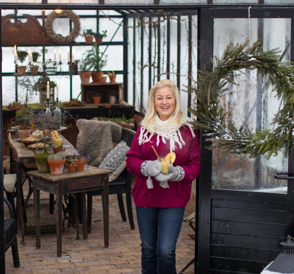 Musta kasvihuone, jossa kaksi tuolia ja pöytä, nainen seisoo kasvuihuoneen ovella.